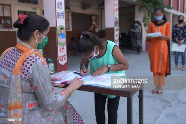 Student wearing a facemask as a preventive measure against the Covid-19 coronavirus submits her national scholarship portal registration form at a...