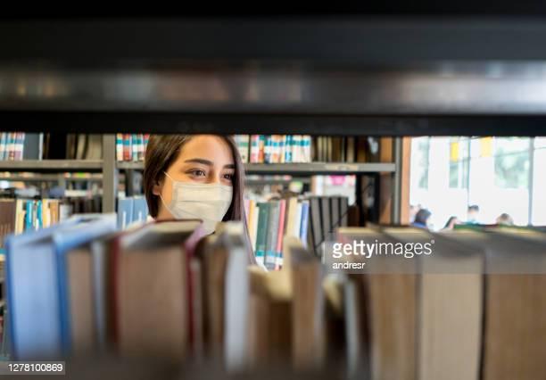 student die een facemask bij de bibliotheek draagt terwijl het zoeken van een boek - bibliotheek stockfoto's en -beelden