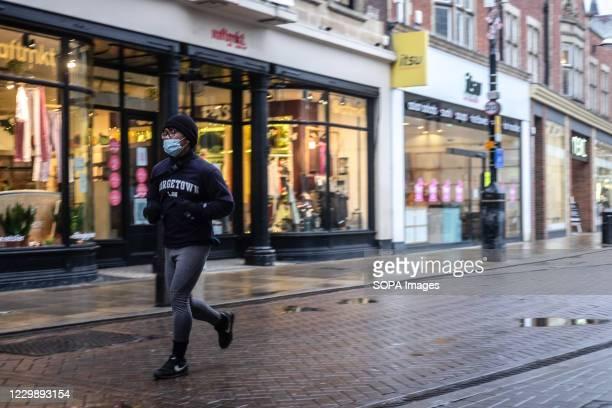 Student wearing a facemask takes a run through the Cambridge city centre.
