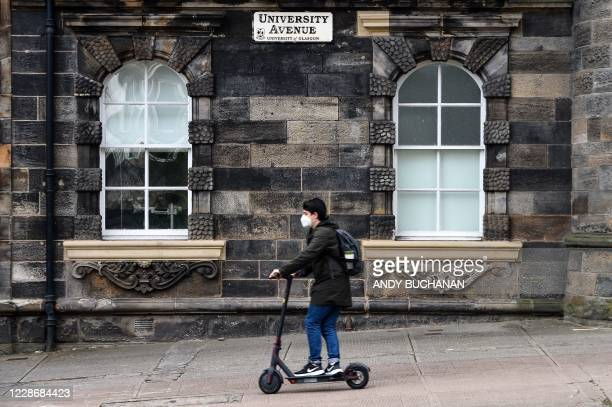 Student wearing a facemask uses an e-scooter as he passes the campus of Glasgow university complex, Glasgow, Scotland on September 24, 2020. - An...