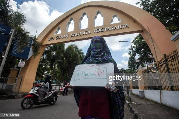 TOPSHOT A student wearing a niqab face veil stages a protest against the ban on wearing niqabs on university grounds at the Sunan Kalijaga State...