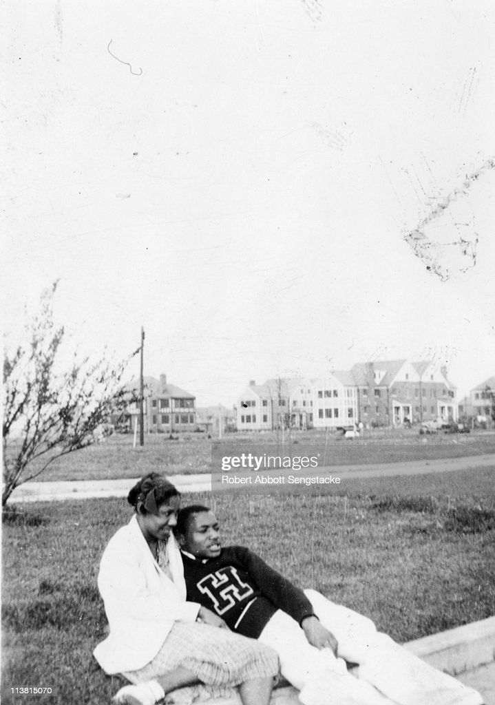 A student, wearing a sweater from Hampton Institute (now Hampton University), relaxes on the grounds with a lady friend, Hampton, VA, early twentieth century.