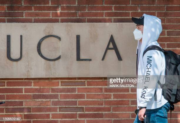 Student wears a face mask to protect against the COVID-19 as he leaves the campus of the UCLA college in Westwood, California on March 6, 2020. -...