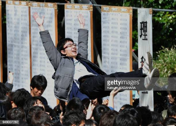 Student who passes an entrance examination of Tokyo University, is tossed in the air to congratuate at school campus, Thursday. Total 3009 students...
