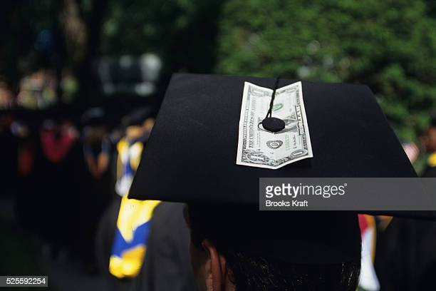 A student with a dollar bill attached to hi cap during the graduation ceremony at Harvard Business School in Boston Harvard Business School is one of...