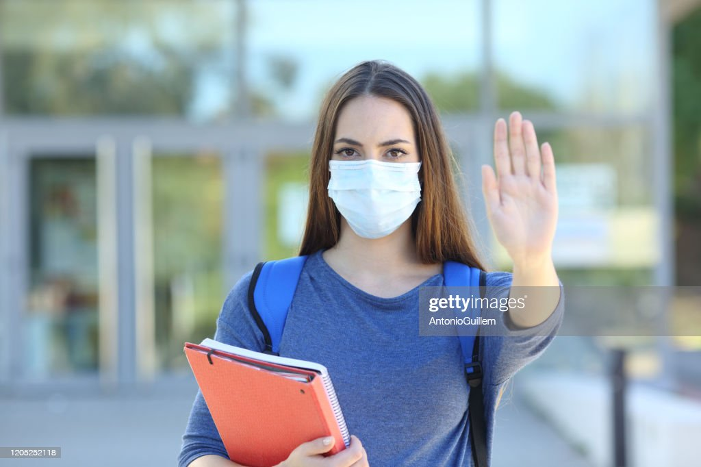 Student with a mask gesturing stop : Stock Photo