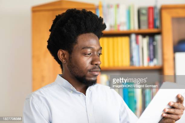 student with afro look learning in library, freiburg, baden-wuerttemberg, germany - sigrid gombert stock-fotos und bilder
