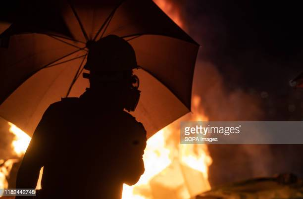 Student with an umbrella and a gas mask close to a burning barricade during the demonstrations An unprecedented battle took place at the Chinese...