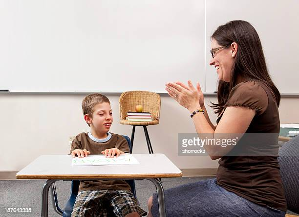 Student with Disabilities and a Teacher Working Together at Desk