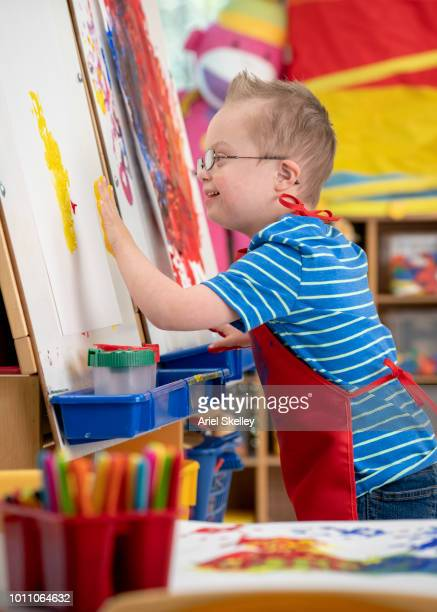 Student with Down Syndrome Finger Painting in Classroom