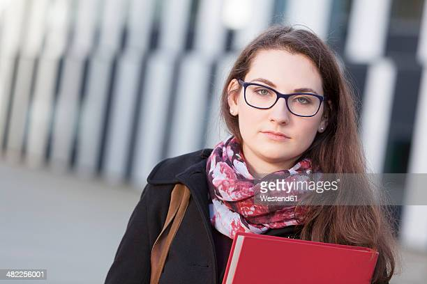 Student with folder outdoors, portrait