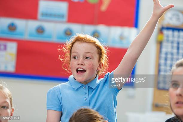 student with her hand up in class - redhead stock pictures, royalty-free photos & images