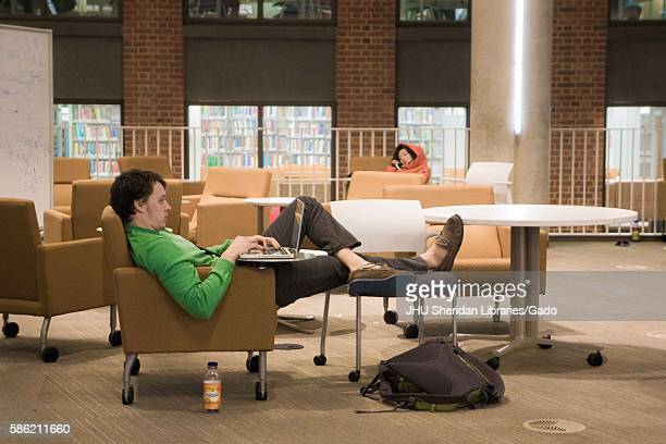 A student with his feet up studies on his laptop while his peer naps nearby on the ground floor of the Brody Learning Commons an...