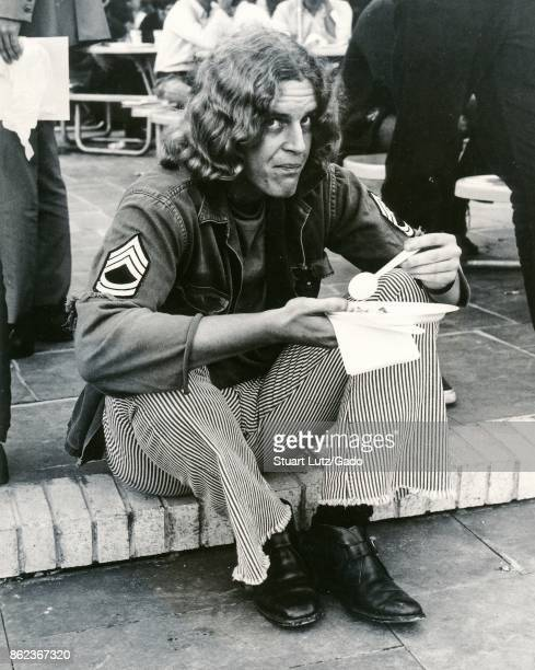 A student with long hair wearing hippie attire including a disheveled United States Army uniform sits on a step and eats during an anti Vietnam War...