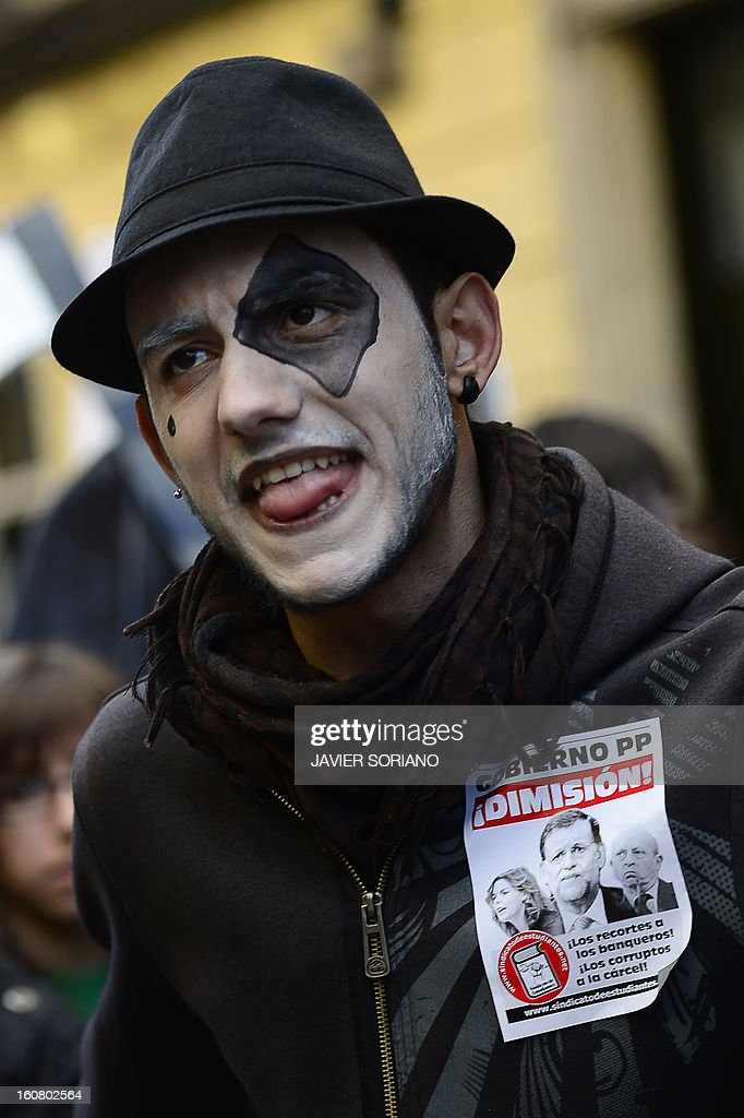 A student with make-up on his face and a sticker reading 'Resignation' and depicting members of PP (Popular Party) reacts as he demonstrates against the law of Spanish Minister of Education, Culture and Sport Jose Ignacio Wert in Madrid on February 6, 2013.