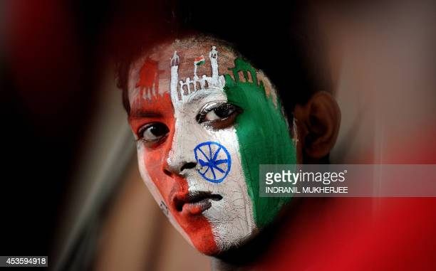 A student with social message and the colours of the Indian tricolour painted on his face waits for the paint to dry on the eve of India's...