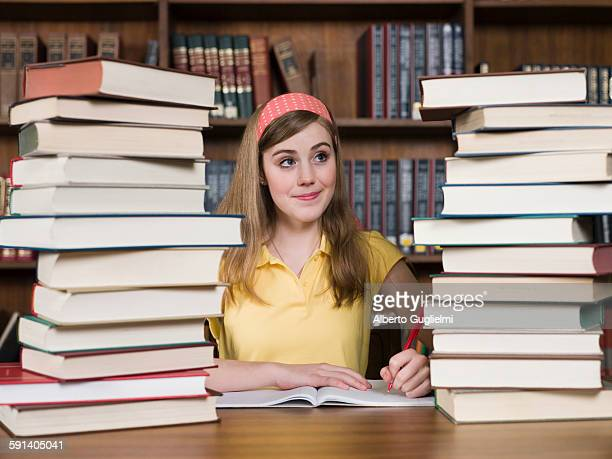 Student with stacks of books at desk in library