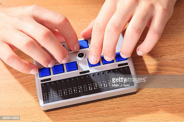 student with visual impairment using her braille display to communicate - braille stock photos and pictures