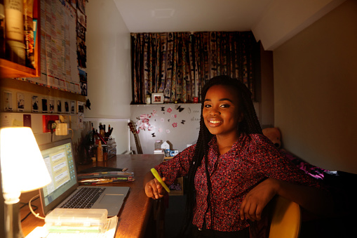 Student working at desk in bedroom at night - gettyimageskorea