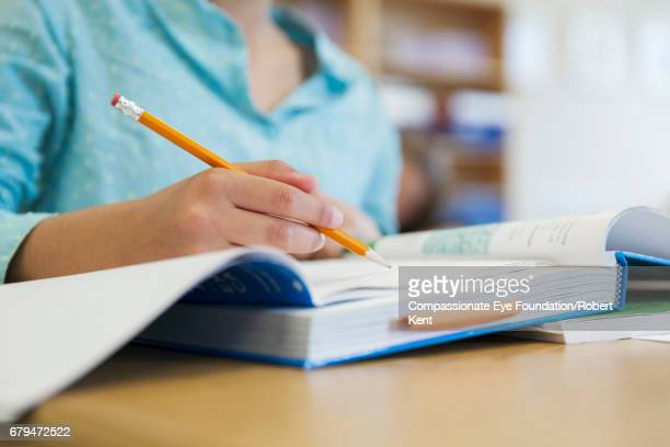 student working in classroom - schulbuch stock-fotos und bilder