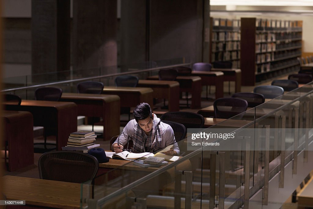Student working in library at night : Stock Photo