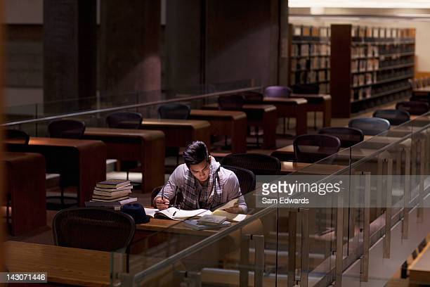 student working in library at night - studeren stockfoto's en -beelden