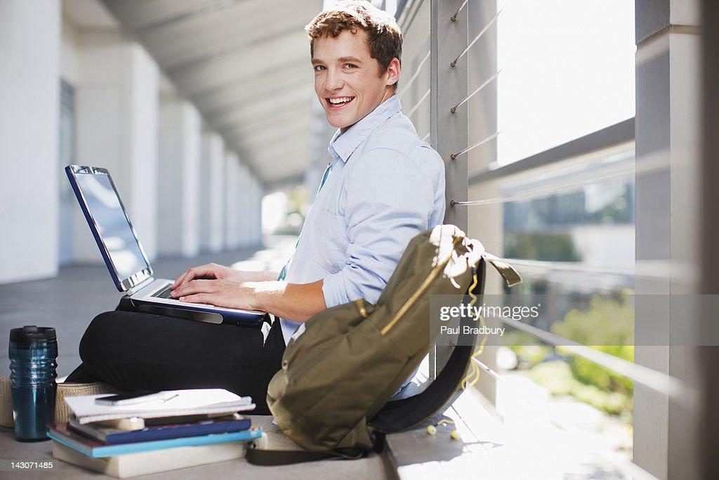 Student working on laptop on floor : Stock Photo