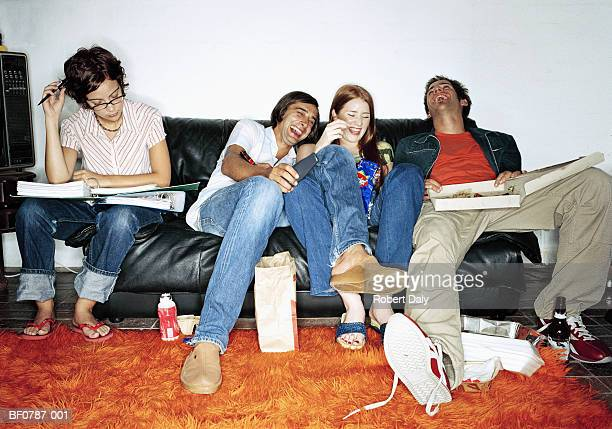 Student working on sofa beside friends eating pizza and laughing