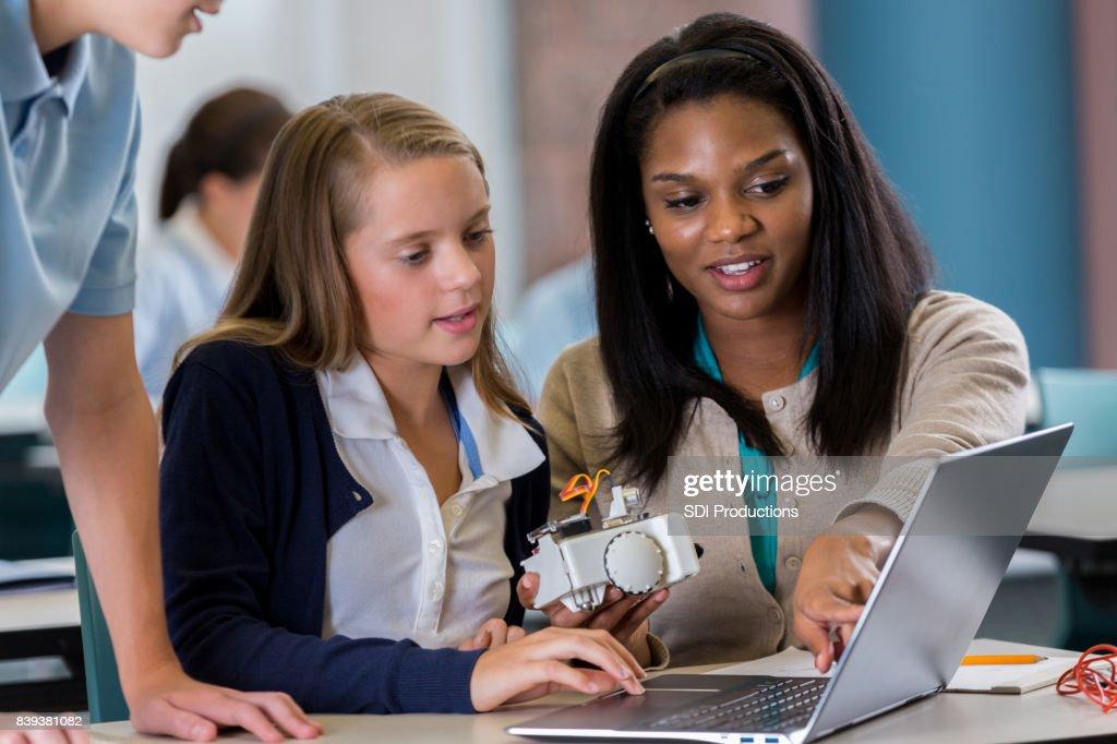 Student works on laptop with teacher in robotics lab : Stock Photo