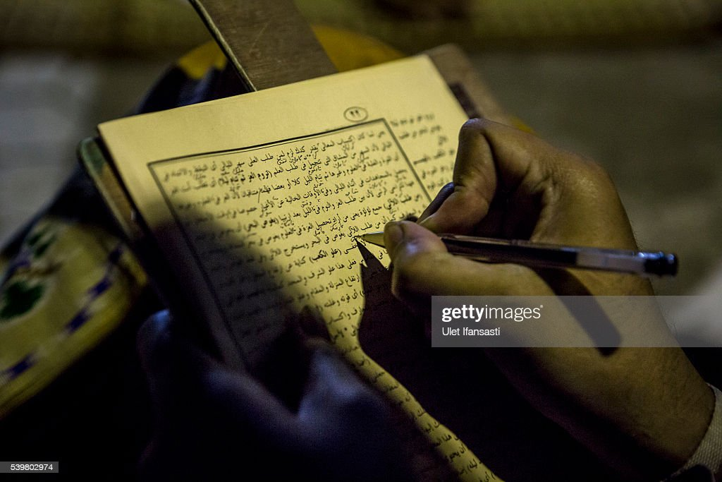 A student writes in Arabic as they learn Islamic scriptures at the islamic boarding school Lirboyo during the holy month of Ramadan on June 10, 2016 in Kediri, East Java, Indonesia. The Islamic boarding school, Lirboyo, was founded by KH Abdul Karim in 1910, and known to be one of the largest traditional 'Pesantren' in Indonesia, with around 17,000 students in Kediri, East Java. Students at the Pesantren, also known as 'Santri', are separated from their families and spend their days studying Islamic scriptures, reading the Quran and learning Arabic in addition to other activities which begins with the morning prayer at 4am till midnight.