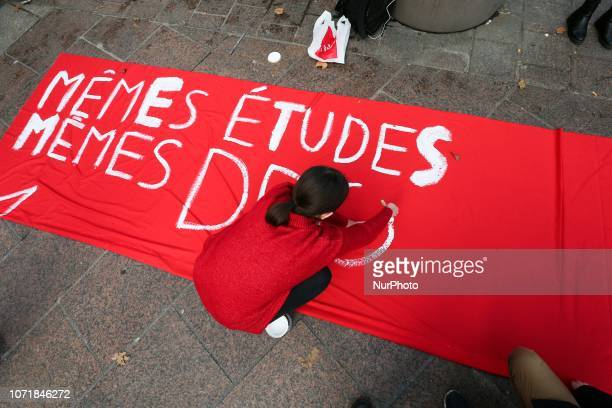 A student writes on a banner « same studies same rights » during a demonstration at Place SaintMichel Paris France on December 11 to protest against...