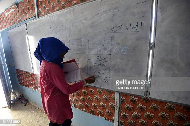 A student writes on a blackboard during class at a school in the Smara refugee camp in Algeria's Tindouf province on February 25 2016 The Western...