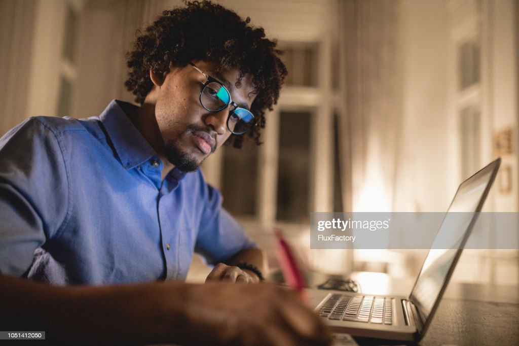 Student writing an essay a night before the exam : Stock Photo
