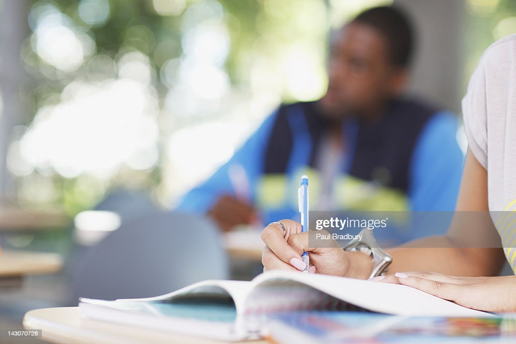 Student writing at desk : Stock Photo