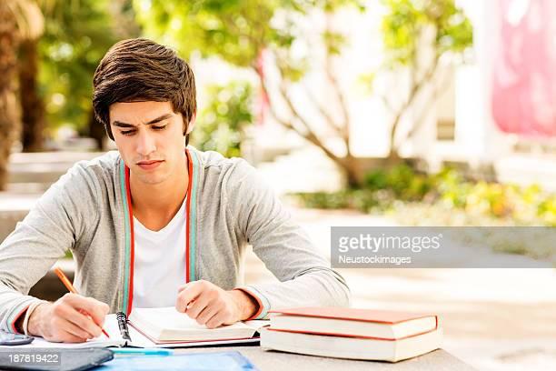 Schüler schreiben In Buch beim sitzen am Tisch, auf dem Campus