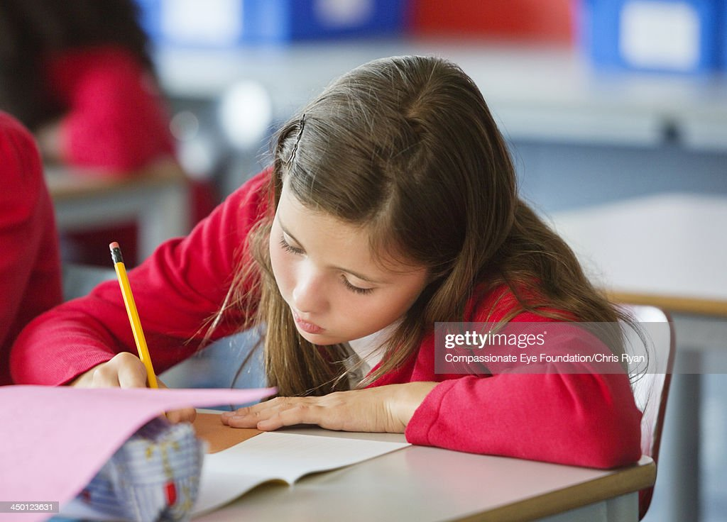 Student writing in classroom : Stock Photo