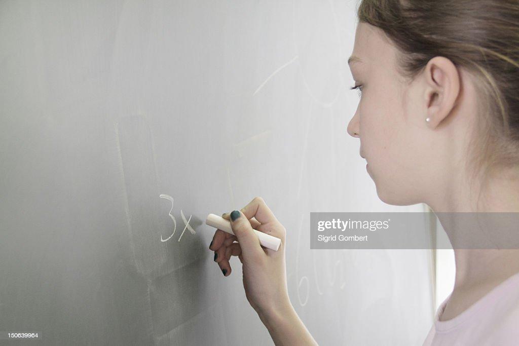 Student writing math on chalkboard : Stock-Foto
