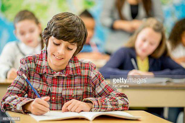 Student Writing on His Notebook in Class