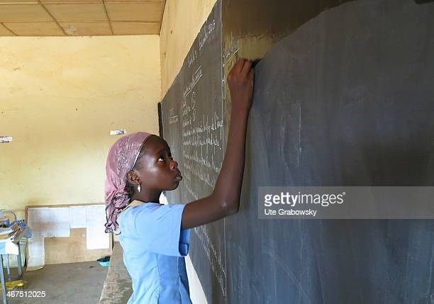 Student writing on the blackboard of a Nigerian school on December 09 in Niamey, Niger. Photo by Ute Grabowsky/Photothek via Getty Images)
