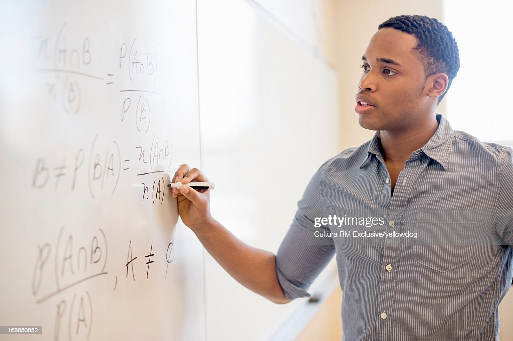 Student writing on whiteboard in class : Stock Photo