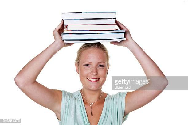 Studentin einer Universität mit einem Stapel Büchern auf dem Kopf