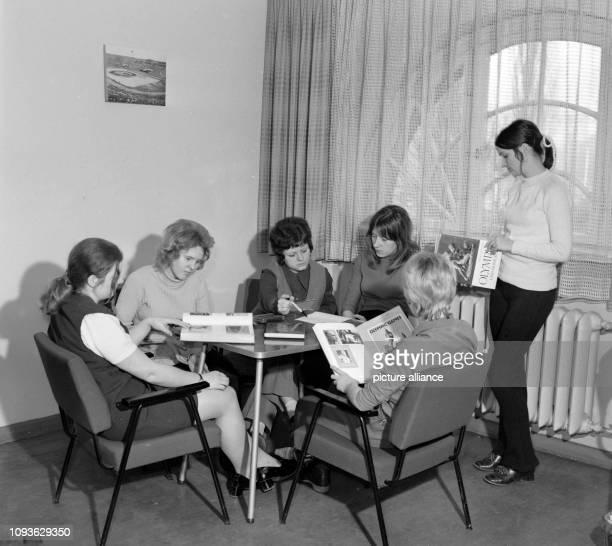 Studentinnen der Universität Jena sitzen mit Büchern zum Thema Olympische Spiele an einem Tisch in einem Freizeitraum aufgenommen am Foto...