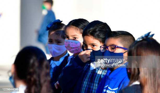 Students adjusts her facemask at St. Joseph Catholic School in La Puente, California on November 16 where pre-kindergarten to Second Grade students...