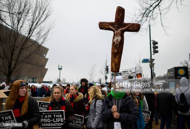 Students and activists carry signs during the annual prolife campaign march in Washington DC on January 18 2019