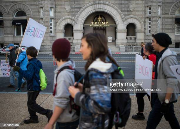 TOPSHOT Students and activists display posters and chant slogans as the pass by the Trump hotel during the March For Our Lives rally against gun...