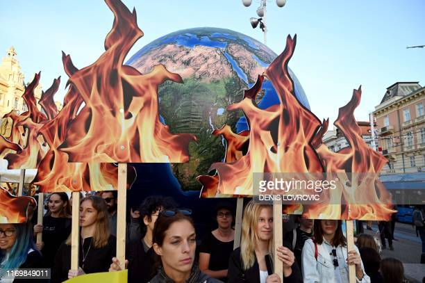 Students and activists hold up a globe as they take part during the Global Climate Strike march downtown Zagreb, Croatia, on September 20, 2019. -...