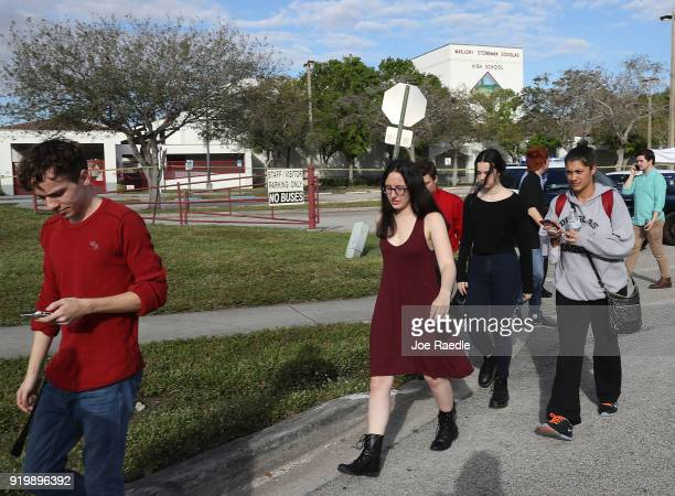 Students and alumni of Marjory Stoneman Douglas High School walk past the school on February 18 2018 in Parkland Florida Police arrested 19 year old...