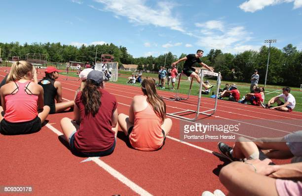 Students and coaches watch while Olympic track athlete Johnathan Cabral runs the hurdles during an instructional practice with former Kennebunk High...