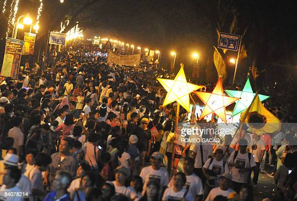 Students and faculties parade with colorful starshaped lanterns during the University of the Philippines' lantern parade as part of the annual...