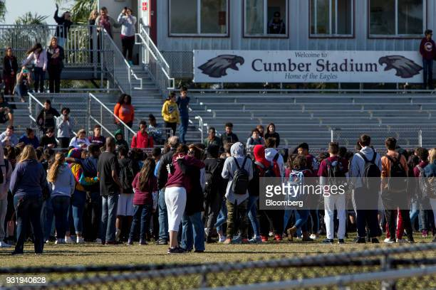 Students and faculty stand outside during the ENOUGH National School Walkout rally at Marjory Stoneman Douglas High School in Parkland Florida US on...